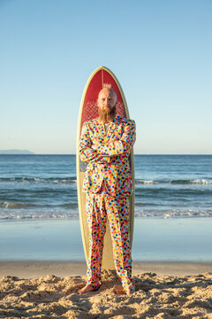 Fashionable man with arms crossed standing against surfboard at beach