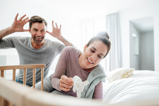 Playful mature couple sitting by crib on bed at home