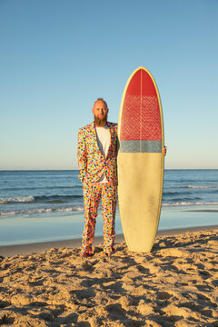 Fashionable man in colorful suit holding surfboard while standing with hands in pockets at beach
