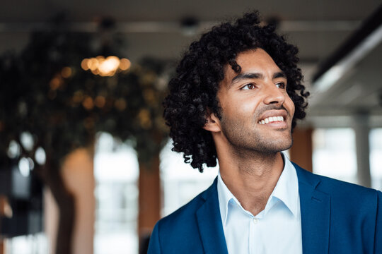 Smiling handsome young businessman with curly black hair looking away at office