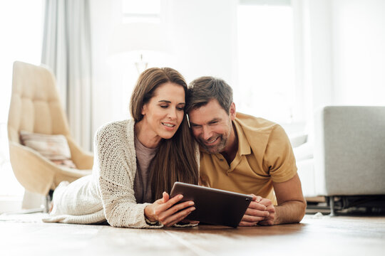Smiling mature couple using digital tablet together while lying on front in apartment