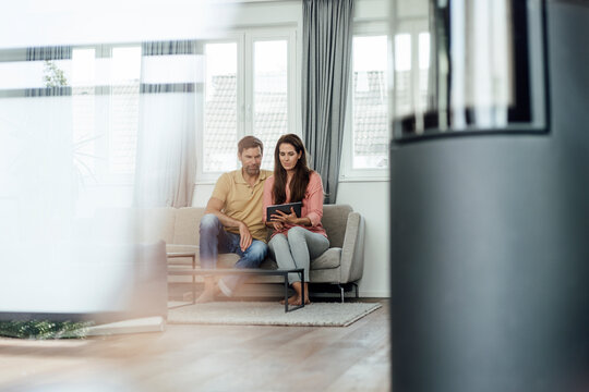 Mature couple using digital table while sitting on sofa in apartment