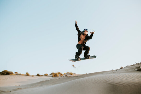 Man sandboarding over sand dunes at Almeria, Tabernas desert, Spain