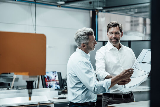 Mature entrepreneurs discussing over business plan while standing at industry