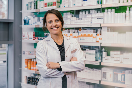 Confident female pharmacist with arms crossed in chemist shop