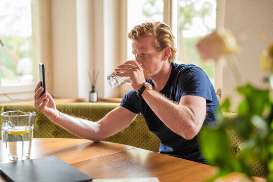 Man drinking water while on video call at home