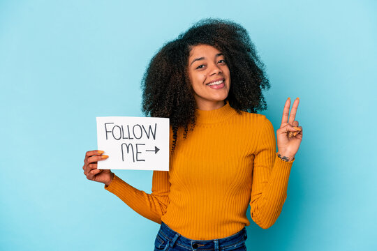 Young african american curly woman holding a follow me placard showing number two with fingers.