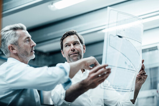 Businessman discussing over business plan with partner while standing at industry