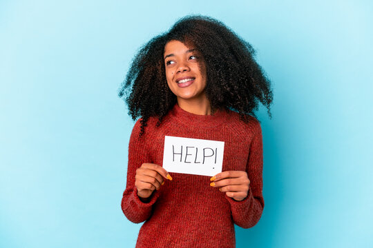 Young african american curly woman holding a help placard looks aside smiling, cheerful and pleasant.