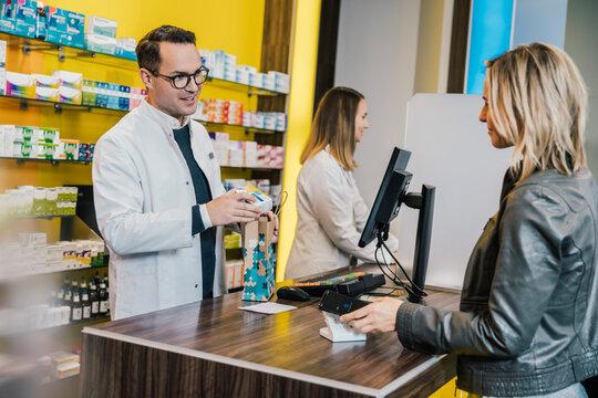 Smiling female customer giving prescription to salesman in chemist store