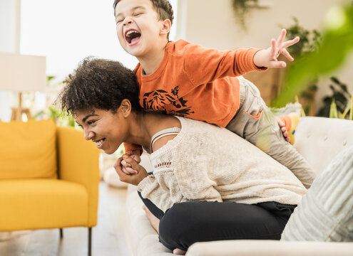 Happy son piggybacking on mother while playing at home