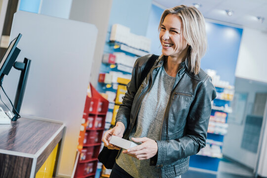 Smiling female customer with medicine standing at checkout counter in chemist shop