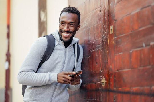 Young man with backpack and mobile phone smiling while leaning on wall