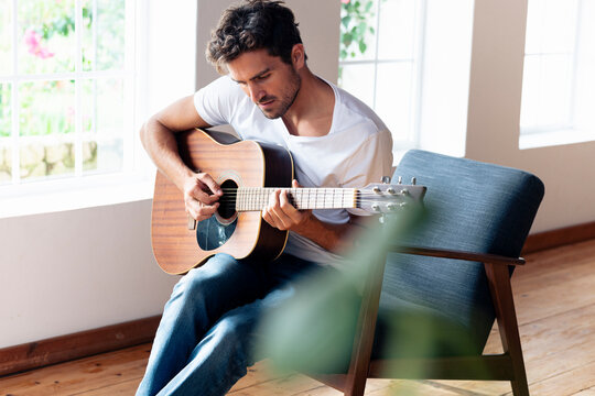 Man practicing on guitar while sitting on armchair at home