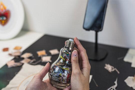 Female craftsperson holding bottle shaped of light bulb in studio