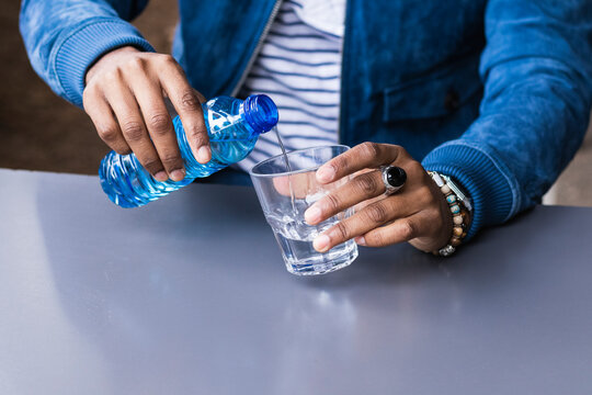 Close-up of mid adult man pouring water in glass on table at sidewalk cafe