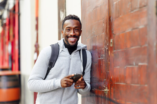 Man with backpack and mobile phone smiling while leaning on wall
