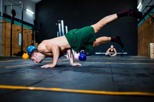 Shirtless young man balancing on floor while woman resting in background at gym