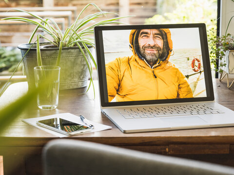 Photograph of mature man on laptop screen at home