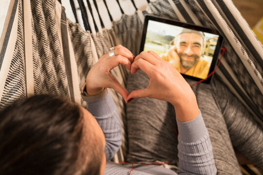 Mature woman showing heart shape sign on video call to man through digital tablet