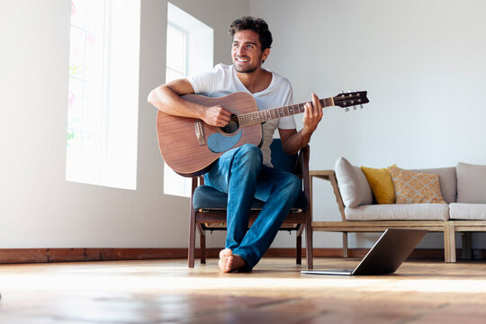 Smiling man playing guitar while sitting on chair at home