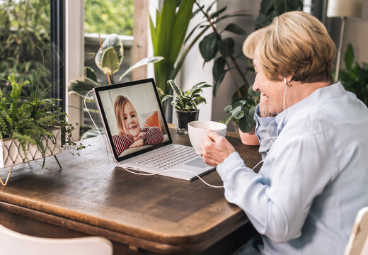 Smiling grandmother on video call with grandchild through laptop while having black coffee at home