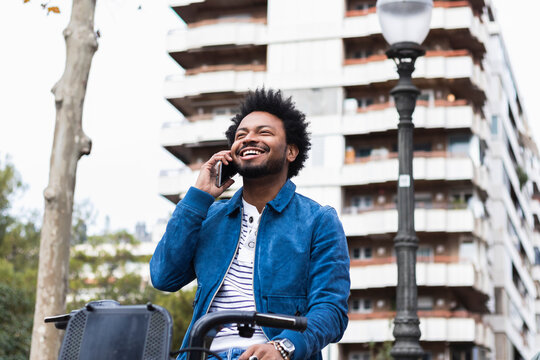 Cheerful man with afro hair talking over mobile phone while sitting on bicycle against building