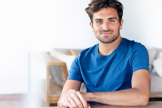 Mid adult man with blue eyes smiling while sitting at home