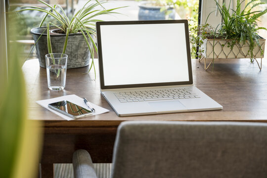 White device screen of laptop by glass on table at home