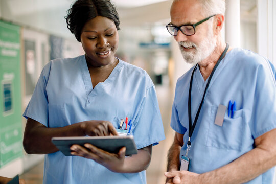 Smiling female nurse showing digital tablet to senior colleague in hospital