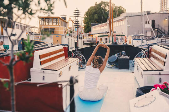 Woman doing stretching exercise on houseboat at harbor