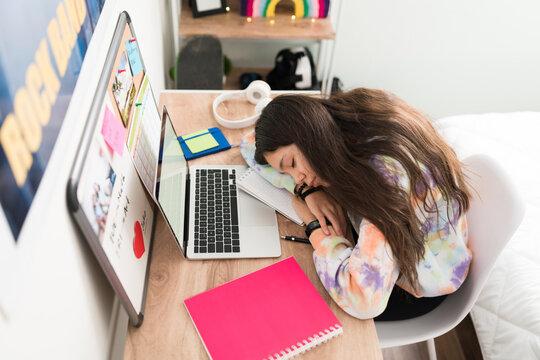 Teen girl dozed off on her desk while doing homework