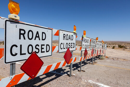 Desert highway road closed signs and barricades near Route 66 in the Southern California.