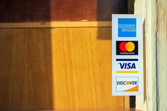American Express, MasterCard, VISA, Discover payment options advertised on a restaurant door. - San Francisco, California, USA - 2020