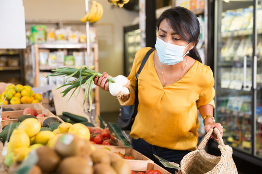 Confident hispanic woman wearing protective face mask to prevent viral infection buying fresh vegetables and fruits in supermarket. New lifestyle in pandemic