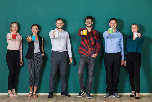 Group of six businesspeople colleague in modern company standing together in a row in front of the green wall and holding coffee cups in hands and give them forward.