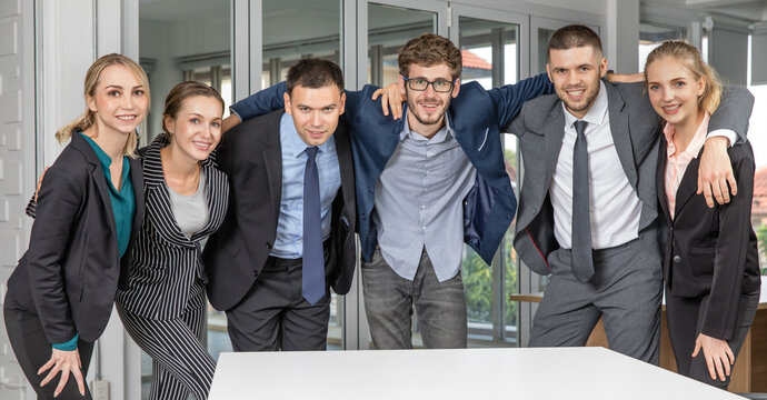 Group portrait of six business people team standing together in an office and cuddle around necks together with smile faces and self-confidence. Idea for success of teamwork in modern business