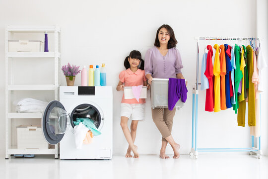 asian mother and cute daughter holding basket of clothes standing and smile between a washing machine and cloth rack in a laundry room at home. Holiday and family concept.