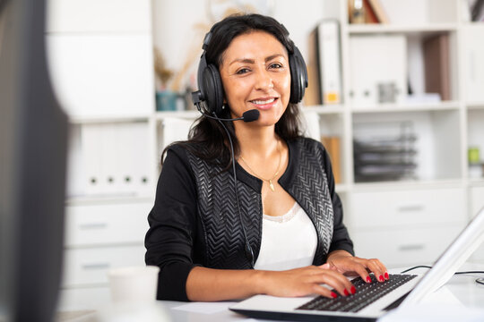 Portrait of positive latin american woman customer support phone operator at workplace