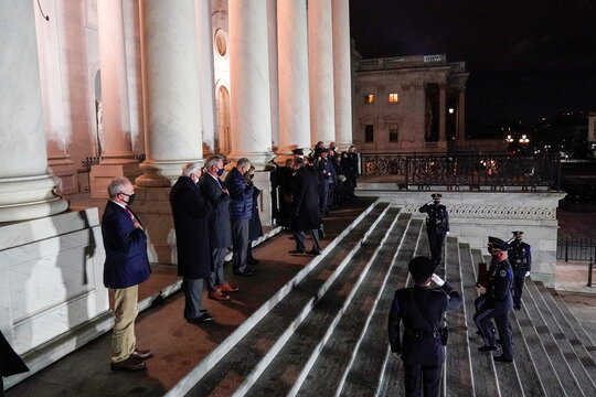 An honor guard carries an urn with the cremated remains of U.S. Capitol Police officer Brian Sicknick and a folded flag up the steps of the U.S Capitol to lie in honor in the Rotunda, in Washington
