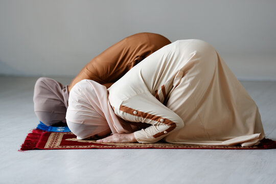 Two Muslim women in beautiful hijab dress standing praying together. Idea for faith and trust in god