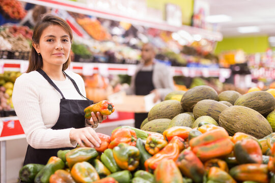 Saleswoman in supermarket of Latin American origin checking product