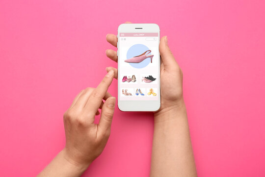 Female hands holding mobile phone with open page of online shoe store on screen against color background