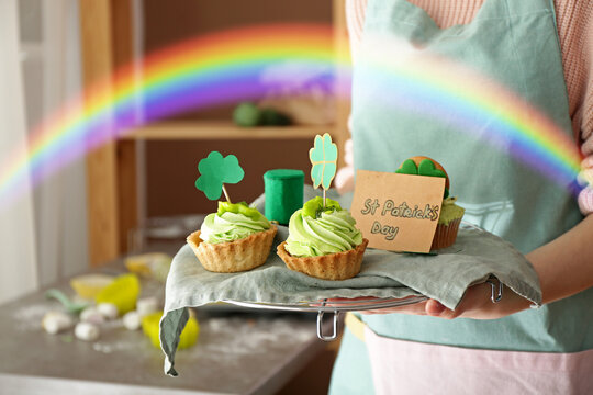 Woman with tasty cakes for St. Patrick's Day in kitchen