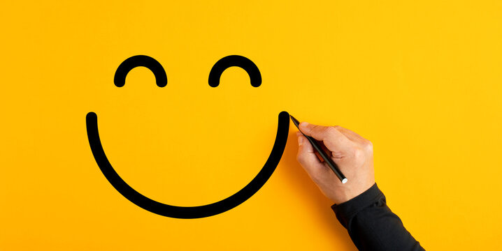 Male hand drawing a smiling happy face sketch on yellow background. Client satisfaction, service or product evaluation