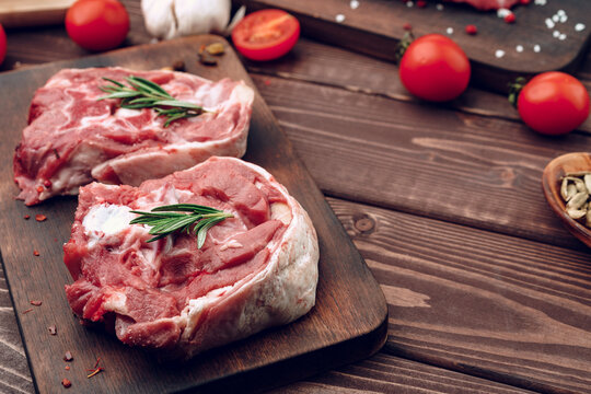 Raw meat beef shank slices on brown wooden board