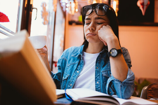 Sleepy young woman student sits at cafe table