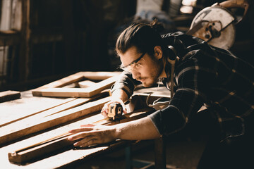 Fototapeta Carpenter man attend to making masterpiece woodworks handcrafted furniture fine measure in wood workshop. obraz