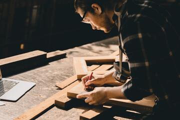 Fototapeta Carpenter man woodcraft working in furniture wood workshop with professional skill real people workman. obraz