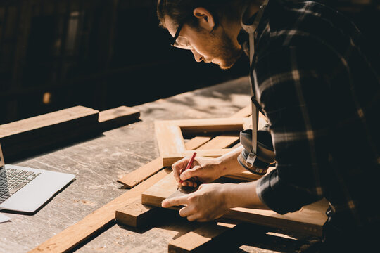 Carpenter man woodcraft working in furniture wood workshop with professional skill real people workman.